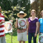 a picture of volunteers that planted a crab apple tree holding small banners for Get Rooted in Cumberland