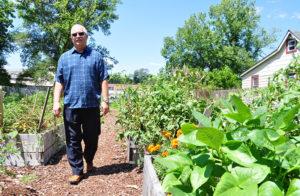 Man walking next to raised garden beds in community garden